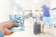 Business woman hand holding American dollar Currency isolated on blurred background travelers walking with a luggage at airport terminal, travel cost concept