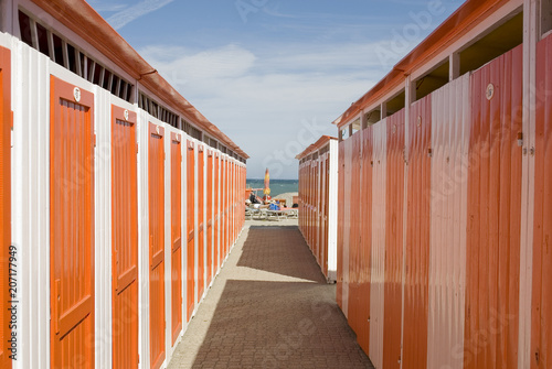 Photographie  wooden beach cabins by the sea, changing rooms, orange and white, used to change
