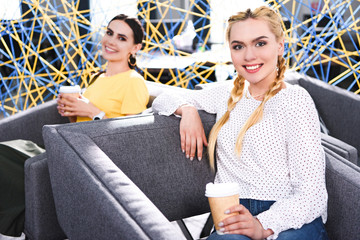 Naklejka smiling businesswomen with paper cups of coffee at modern coworking office