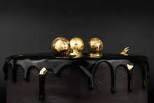 Chocolate Cake With Black Glaze, Decorated With Balls In Gold On A Black Background. Picture For A Menu Or A Confectionery Catalog.