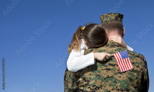 Fototapeta Military Father Hugging His Daughter With An American Flag