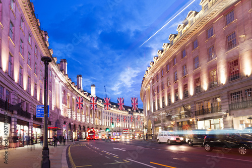 Poster Londres bus rouge Popular tourist Regent street with flags union jack in night lights illumination in London, England, United Kingdom