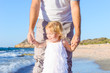 Close up happy child girl with her father holding hands and having fun walking on the beach. Family vacation, travel concept. Bright sunlight. Copy space.