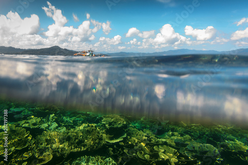 Fotografía  Above and below waterline with clouds reflected on water surface and sandy seabe