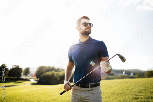Leinwand Poster Golf player holding a golf club in golf course
