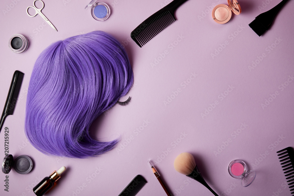 Fototapeta top view of violet wig, makeup tools and cosmetics on purple
