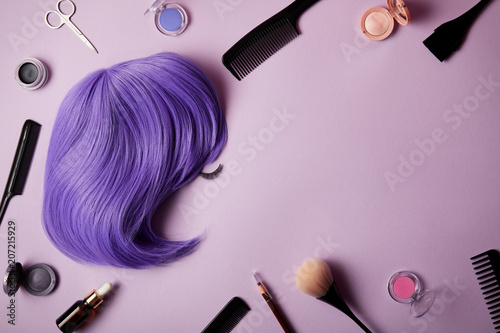 top view of violet wig, makeup tools and cosmetics on purple Canvas