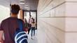 Teenage Students And Teacher Walking Between School Buildings