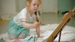 Beautiful red-haired girl sits on the floor in the studio in front of the easel and draws a brush and colored paints