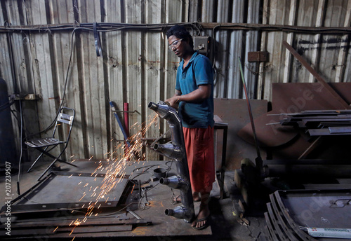 A worker grinds a steel pipe to be used in air ducts inside