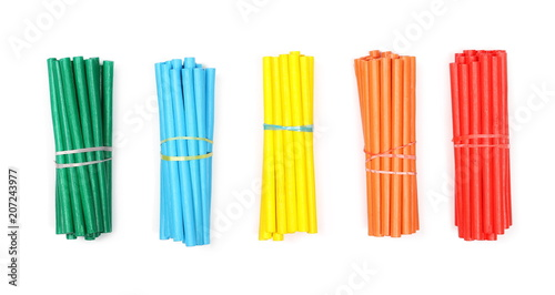 Fotografia  Bundle of colorful decorative sticks isolated on white background, top view