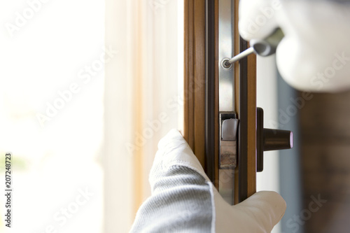 Fototapeta Construction worker installing window in house. Handyman fixing the window with screwdriver obraz