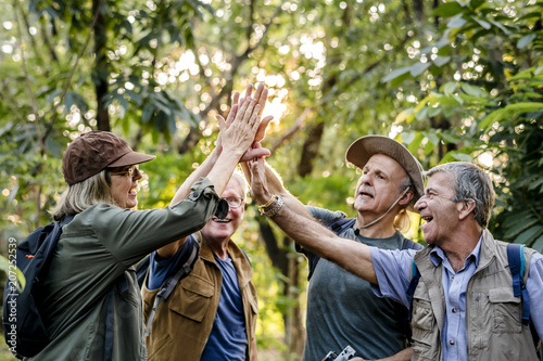 Fototapeta  Senior trekkers giving a high five
