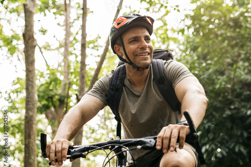 Tuinposter Ontspanning Happy cyclist riding through the forest