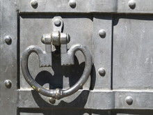 Old Metal Knocker On The Door. Medieval Iron Knocker Ring Forged In The Shape Of A Heart, Painted Black