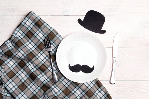 Father's Day table setting with cutlery, hat and mustache on white wooden table. Top view.