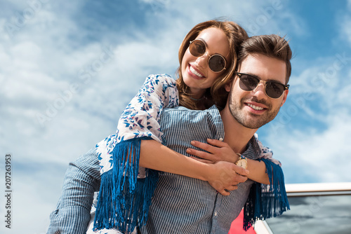 Fototapeta handsome man in sunglasses piggybacking his smiling girlfriend