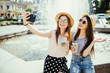 Two cheerful young women pose against fountain with smoothie, make selfie on modern mobile phone or talk online on video call, share their impressions about resort abroad