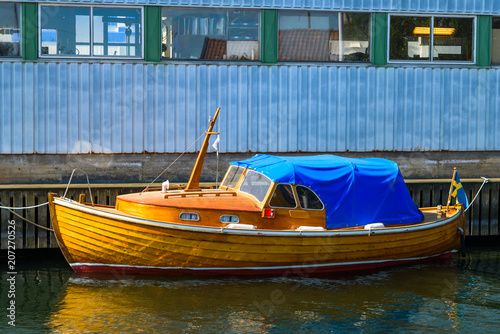 Vintage wooden boat with blue tarp, moored outside an industrial building.
