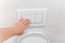 Hand Pressing Toilet Flush Button