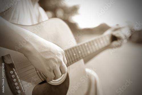 Fotografering  Close-up male hand playing on acoustic guitar outdoor