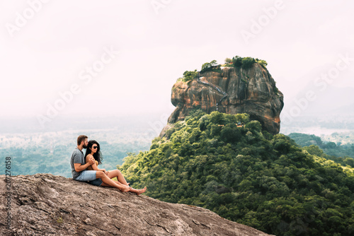 Photo  A couple in love on a rock admires the beautiful views