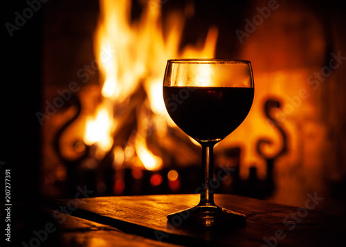 Fotografía Glass of red wine on the wooden table with burning fire on the background