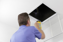 Man Inspecting An Air Duct Wit...