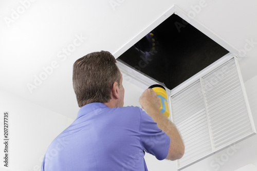 Fotomural Man Inspecting an Air Duct with a Flashlight