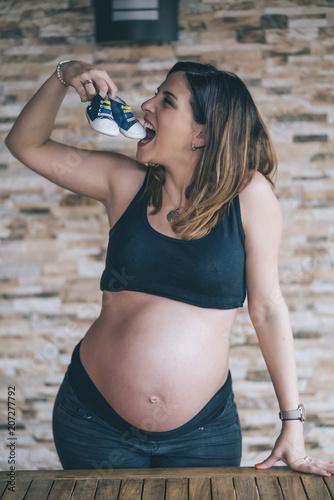 Fotografia  Pregnant pretty woman shows small baby shoes.