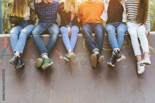 Summer holidays and teenage concept - group of smiling teenagers with skateboard hanging out outside Wallpaper Mural