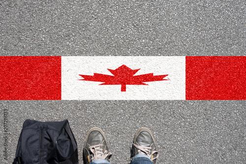 Vászonkép Ein Mann mit dem Koffer steht an der Grenze zu Kanade