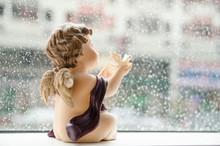 Soft Focus For Little Cupid Holding White Dove Resin In Rain Background.