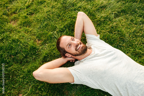 Photo from top of smiling handsome man wearing white t-shirt, spending leisure time in green park lying on grass and putting hands behind his back