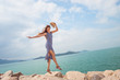 Attractive girl in dress jumps on rocks on beach, toned. Active leisure, Health, tourism, Vacation theme.