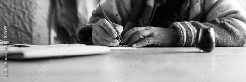 Wide low angle view of an elderly man doing calligraphy writing using a nib pen and ink