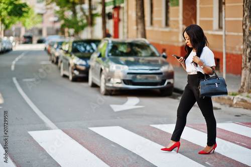 Stylish african american business woman on streets of city at pedestrian crossing Fototapet