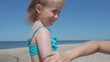Mother applying sunscreen lotion on Daughter at beach. Mother preparing child for bath in sea.
