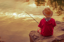 Cute Little Boy In A Hat Is Fishing On The Lake At Sunset. Toned Photo