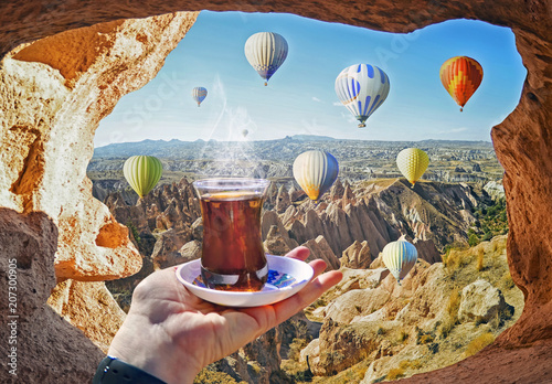 Morning cup of tea with view of colorful hot air balloons flying over the valley at Cappadocia, Turkey. Volcanic mountains in Goreme national park