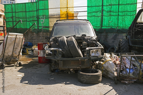 Photo  Front view of a wrecked SUV in a parking lot with garbage in the street of Istan