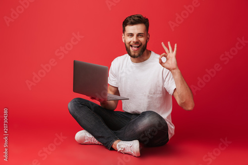 Fotografie, Obraz  Photo of european joyful guy in t-shirt and jeans sitting on floor with legs cro