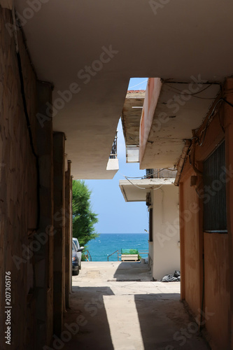 Spoed Foto op Canvas Smal steegje A narrow alley leading out to the turquoise sea. Crete, Greece.