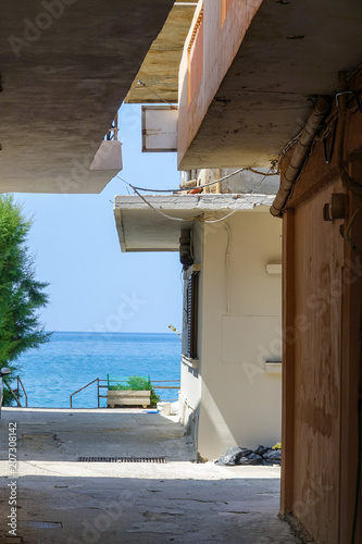 Deurstickers Smal steegje A narrow alley leading out to the turquoise sea. Crete, Greece.