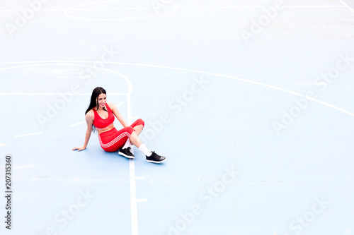 Smiling young woman sitting on sports ground