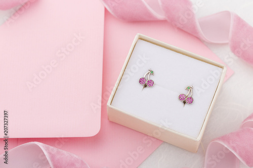 Cherry shaped earrings with crystals in gift box on pink envelope background with copy space