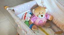 Baby Cot Or Crib With Cute Soft Cuddly Toys And White Blanket