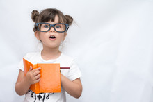 Surprised Cute Child In Eyeglasses, Writing In Notebook Using Pencil, Keeping Mouth Wide Open. Four Or Five Years Old Kid, Isolated On White, Space For Advertising Text