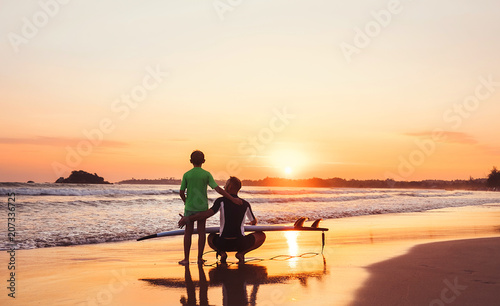 Father surfboarder with his son meet a sunset on the ocean beach