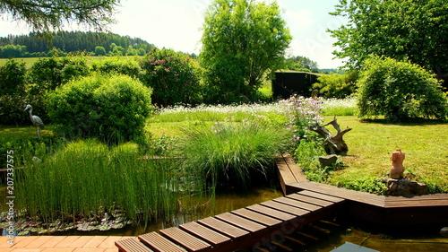 malerischer naturbelassener Garten mit Teich an roter ...